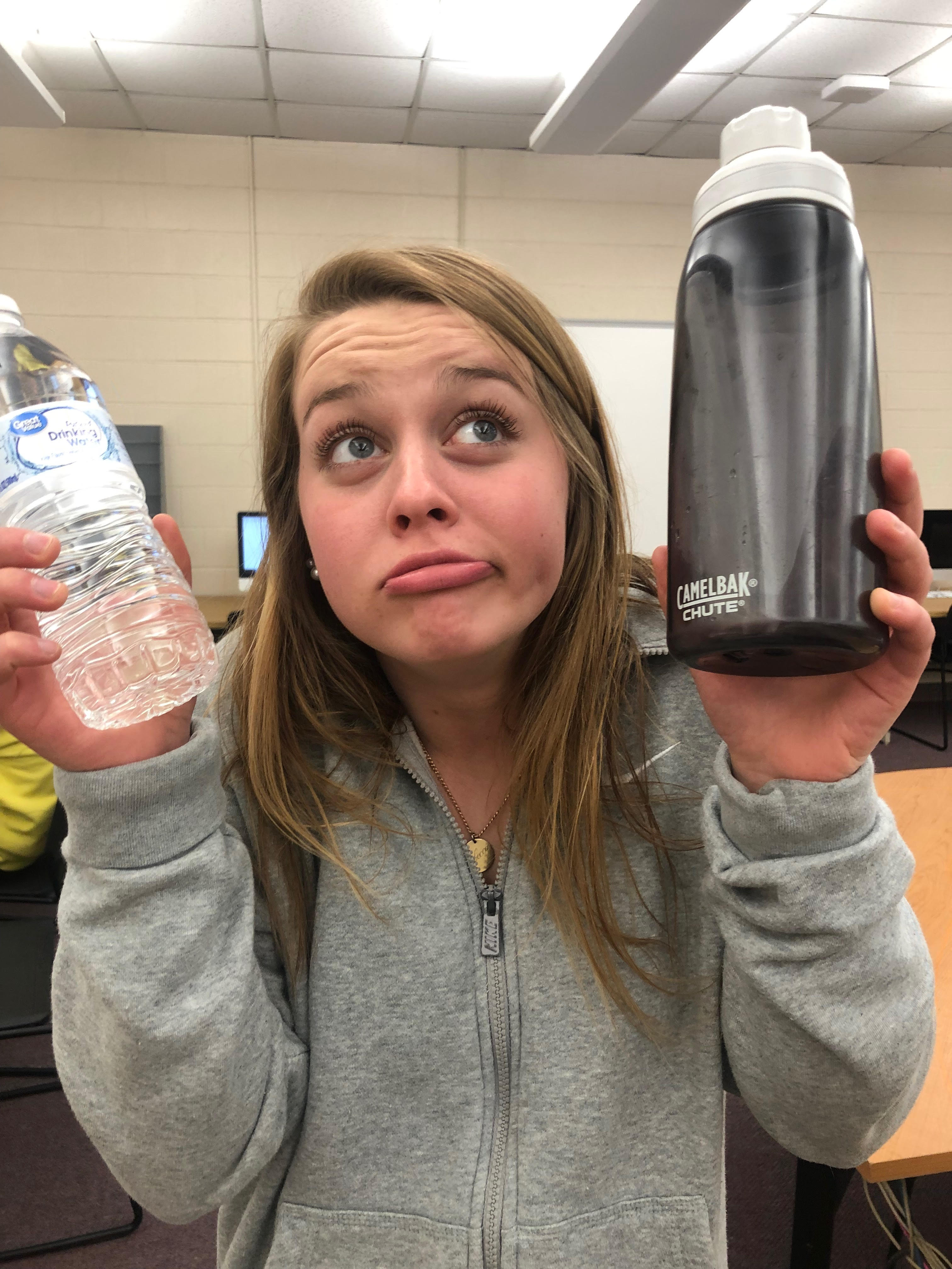 girl holding a plastic water bottle and a reusable water bottle